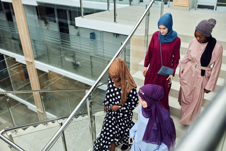 Multicultural group of female Arabian students, dressed in national dresses and scarfs going down the stairs of university , sharing ideas with each other on the way Stock Photo