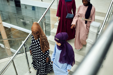 Multiracial group of muslim business women visiting international conference at business centre, walking down the staircase sharing impressions and ideas after event