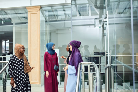 Group of smiling muslim women in hijab walking down the stairs of business centre. Arabian and african ladies dressed in long smart dresses and scarfs going to conference hall Stock Photo