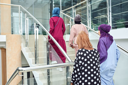 Multicultural group of female Arabian students, dressed in national dresses and scarfs climbing the stairs of university, sharing ideas with each other on the way Stock Photo