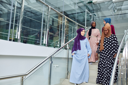 Young muslim cheerful business traveller women in national arabian clothings visiting business centre, climbing up the stairs chatting about their future plans of sightseeing of Dubai