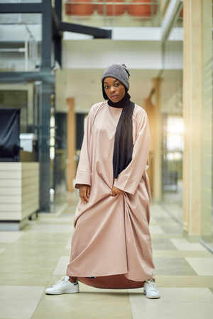 Fashion shot of glamorous african woman dressed in muslim style pink dress with modern hat posing in empty hall