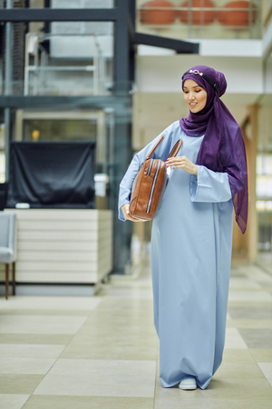Fashion portrait of beautiful young stylish muslim woman wearing violet hijab and blue silk dress standing in modern hotel interior with a lot of glass