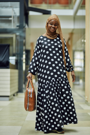 Attractive young african muslim girl wearing stylish dress, golden silk hijab, having happy smile on her face standing with a bag in big shopping mall. Human emotions, facial expression concept.