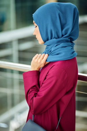 Designers also create fashionable Muslim dresses, keeping the line between religion and fashion. Attractive caucasian woman dressed in custom made muslim dress and hijab on head Stock Photo