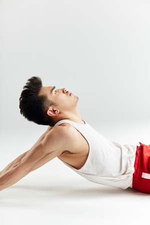 Asian street dancer in red sportive pants warming up before workout in white studio.