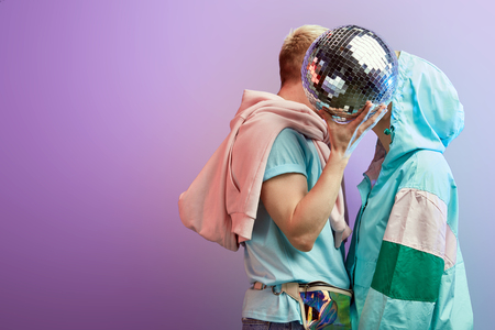 Couple in fashionable clothes kissing hiding from camera behind big mirror disco ball, come to lovers, have good relationships, stand close to eac