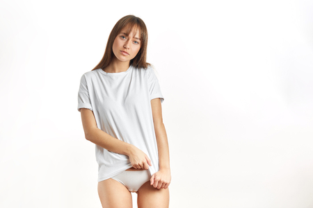 Attractive young woman in oversized white t-shirt, being in underwear, shows perfect slim body and healthy skin, posing over white studio background. Stock fotó