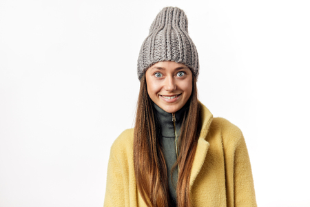 Overjoyed beautiful bug eyed woman expresses happy emotions, has broad pleasant smile, dressed in warm topcoat and fashionable hat, poses isolated over white background Stock fotó - 123239666