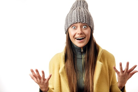 beautiful bug eyed woman expresses happy emotions and surprise, as if can not believe, that she dressed in warm topcoat and fashionable hat, poses isolated over white background