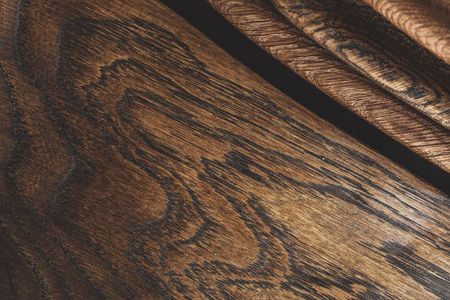 Wood texture, close up. Showing growth rings. Design boards made of solid wood. Set of cutting boards and wooden dishes made from of valuable timber on dark background.