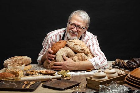 An old happy professional baker who loves his business and the products he bakes, sits at the table, surrounded by loaves of fresh organic bread, welcoming to taste it. Banco de Imagens - 123407408