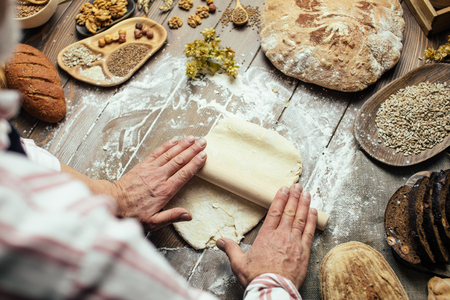 Different kinds of fresh bread, focaccia, typical Italian bread with crispy and very tasty crust and male hands rolling out dough for Italian pizza. Healthy eating and traditional bakery concept. Stockfoto