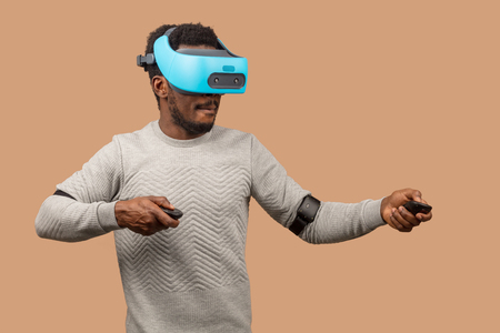 Dark skinned male gamer wearing virtual reality goggles, playing 3d game, isolated against studio beige wall.