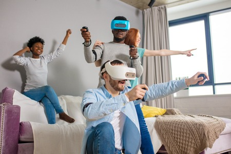 Group of multiracial male amd female students playing virtual game using vr goggles, having fun together ay home - Virtual omg reality and portable digital technologies