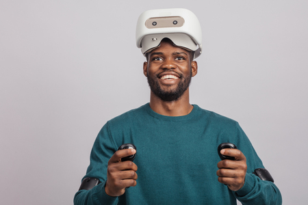Young dark skinned guy getting excited after watching 3 D film using virtual reality headset, looking at camera isolated in green wear over grey background. Stock Photo