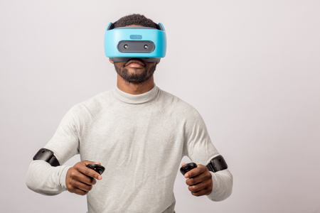 Dark skinned confident man with a short stubble, dressed in white, wearing blue mobile virtual reality headset holding hands as if he is driving car isolated over white background. Stock Photo