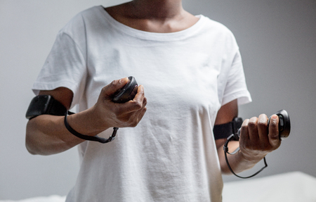 Mid-section of a dark-skinned woman, dressed in white t-shirt, holding remote controllers from virtual reality gadget. Focus on hands, Isolated studio shot of VR technology gadget.