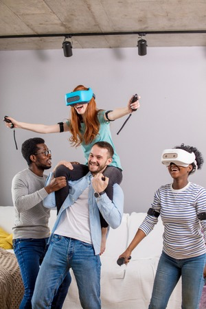 Two excited multiracial student couples having fun engaging in virtual reality game where girls surfing in the ocean in virtual world and guys helps them to feel 5 Dimension at once, piggybacking one