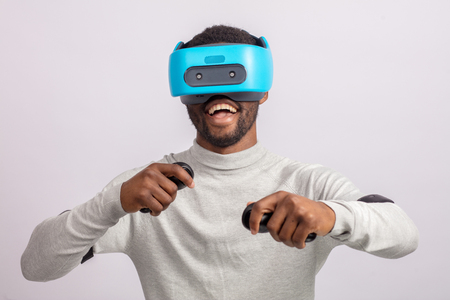 African guy in casual wear plays racing game in VR headset, holding hands with controllers raised as if he is driving car on high speed in virtual reality.