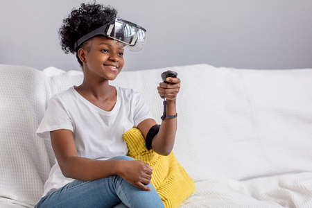 Happy pleasantly looking dark-skinned female teenager in white t-shitr, wearing mobile virtual reality headset and holding joystick, makes settings for playing VR games