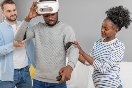 Professional caucasian gamer gives masterclass to african couple amateurs to master head head-mounted display, device for virtual 3 D gaming Stockfoto