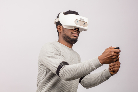Dark skinned ethnic man using virtual reality glasses watching a simulation image 3D, holding gamepads in raised hands as if he plays Car Race