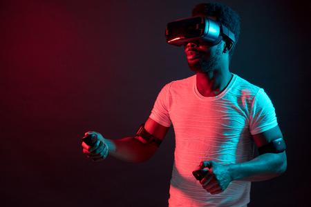 Giovane che indossa la cuffia VR e sperimenta la realtà virtuale. Luce rossa bicolore blu su sfondo nero.