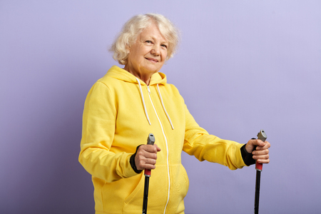 Senior woman in yellow sports suit standing with Nordic walking poles in violet studio. Concept of healthy and active lifestyle of elderly people Reklamní fotografie