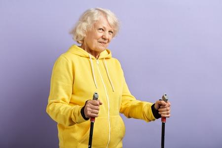 Ältere Frau im gelben Sportanzug, die mit Nordic-Walking-Stöcken im violetten Studio steht. Konzept des gesunden und aktiven Lebensstils älterer Menschen
