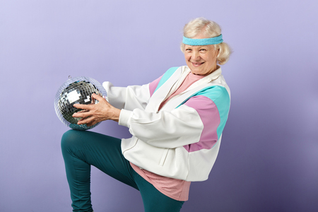 Positive glad elderly lady holds sparkling disco ball, dressed in trendy windbreaker of mint and pink colors, smiling at camera, being in high spirit