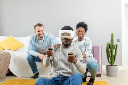 Amazed shoked surprised african man wearing virtual reality glasses while two diverse multiracial friends sitting on couch and smiling