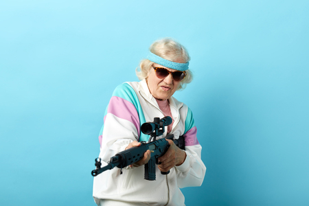 Experienced female agent working undercover of a grandmother-dandelion is pointing a rifle at the camera, standing isolated on blue background. Poster. Blue background.