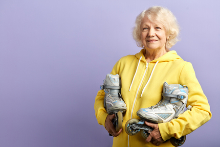 Active senior woman in yellow sports hoodie holding roller-skates posing isolated indoors over violet background. Age, active leisure time concept Banco de Imagens