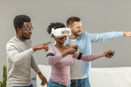 African young woman trying on vr glasses for the first time and her smiling male friends show her the right way to manage it in the room space.