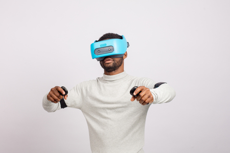 Stylishly dressed african guy using new VR technology headset, learning material and getting knowledge and practice through 3D video glasses. Virtual education concept