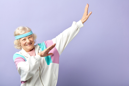 European retired woman in sportive clothing and headband, having beaming with joy face expression gesturing with hands while posing isolated in studio over blue background, copy space