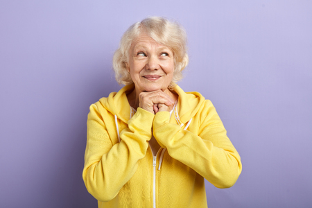 Beautiful looking happy mature woman, smiling and enjoying life, wearing sweatshirt, isolated on purple background with copy space. Wellness, Sport, Age Concept