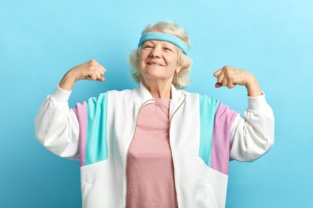 Happy, proud elderly attractive woman flexing both arms in the air with fists pressed showing strength or success, celebrating sport achievements.