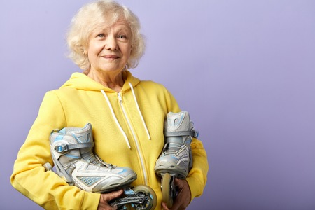 Active senior woman in yellow sports hoodie holding roller-skates posing isolated indoors over violet background. Age, active leisure time concept Фото со стока