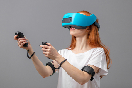 Redhead woman in white t-shirt wearing using headset, experiencing virtual reality while playing video game, isolated over grey background
