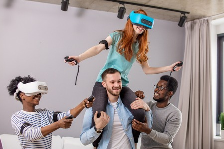 Happy red-haired woman in virtual reality headset is riding piggyback on her boyfriend, surrounded by mixed race friends at home. Dating, romantic relationship and virtual reality technology concept.