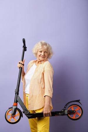 So fun. Happy elderly woman keeps in hands scooter ready for a ride. Studio shot against purple wall Фото со стока