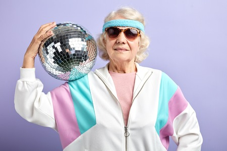 Positive glad elderly lady holds sparkling disco ball, dressed in trendy sunglasses and windbreaker of mint and pink colors, smiling at camera, being in high spirit