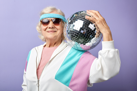 Joyful smiling aged woman portrait dressed in sportswear, holding ball, set in purple studio. Age of health, leisure, entertainment in retirement