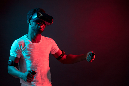 Young man wearing VR glasses watching video or movie, isolated on dark red dual light, testing gadget for virtual reality, isolated on black background with red colour flashes.