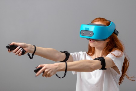 3d technology, virtual reality, entertainment, education concept. Young red-haired woman wearing white t-shirt using vr headset with head-mounted display, playing video game Фото со стока