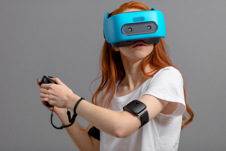 Teenage female in casual wear with VR glasses and joystick having 3D experience, virtual reality concept.
