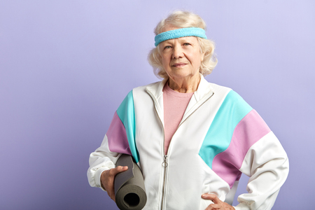 Joyful old woman with mat is going to practice yoga exercises, dressed in white sports jacket and headband, isolated on violet background