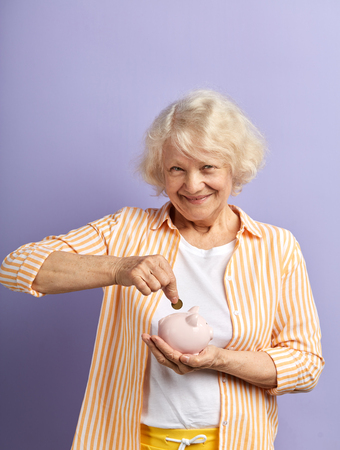 Indoor portrait of happy caucasian mature woman with lovely pleasant smile saving coin into piggy bank. Savings, money, annuity insurance, retirement and people concept